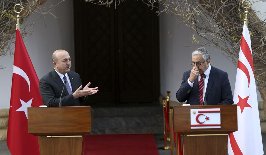 Turkish Foreign Minister Mevlut Cavusoglu, left, and Turkish Cypriot leader Mustafa Akinci talk to the media after their meeting in the Turkish Cypriot breakaway north part of the divided capital Nicosia, Cyprus, Friday Jan. 25, 2019. Cavusoglu is in Turkish breakaway north part of the divided island for talks in two-day visit. (AP Photo/Petros Karadjias)