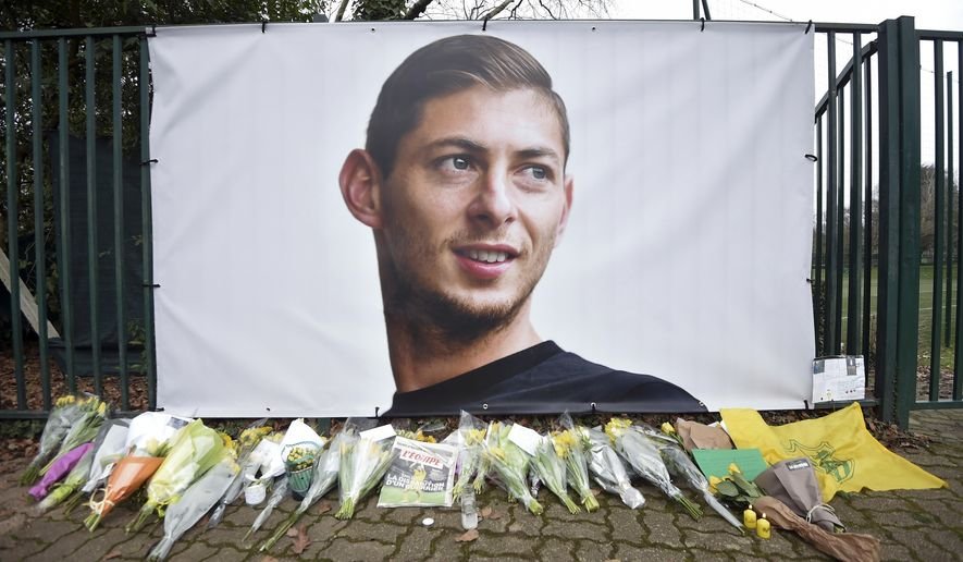 Flowers and tributes are placed near a giant picture of Argentine soccer player Emiliano Sala outside the FC Nantes training camp, in Nantes, western France, Thursday, Jan. 24, 2019, after a plane with Sala on board went missing over the English Channel on Monday night. Sobbing after the active search for her brother was halted, the sister of Argentine soccer player Emiliano Sala urged authorities Thursday not to give up trying to find the remains of his plane that disappeared from radar over the English Channel. (AP Photo)