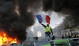 FILE - In this Saturday, Nov. 24, 2018 file picture, a demonstrator waves the French flag onto a burning barricade on the Champs-Elysees avenue with the Arc de Triomphe in background, during a demonstration against the rising of the fuel taxes, in Paris, France. Thousands of demonstrators will again take to the streets across France this weekend in protest of French president Emmanuel Macron's policies, while anti-yellow vests groups have also planned to use street action to condemn violence.(AP Photo/Michel Euler, File)
