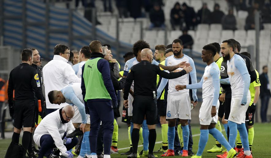 The referee speaks to players as the match is suspended during a French League One soccer match between Olympique Marseille and Lille at the Stade Velodrome in Marseille, France, Friday, Jan. 25, 2019. (AP Photo/Claude Paris)