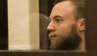 Briton Jack Shepherd sits behind glass in a court room in Tbilisi, Georgia, Friday, Jan. 25, 2019. A court in the ex-Soviet republic of Georgia has ruled to keep Shepherd a fugitive British man for three months behind bars pending possible extradition. (AP Photo/Shakh Aivazov)
