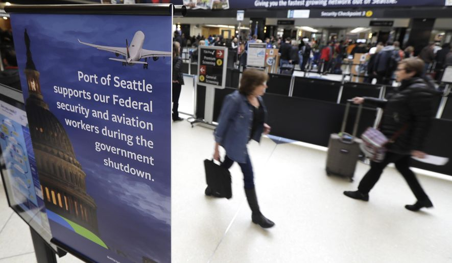 A sign near a TSA security checkpoint states the Port of Seattle's support for federal government workers, Friday, Jan. 25, 2019, in Seattle. Yielding to mounting pressure and growing disruption, President Donald Trump and congressional leaders on Friday reached a short-term deal to reopen the government for three weeks while negotiations continue over the president's demands for money to build his long-promised wall at the U.S.-Mexico border. (AP Photo/Ted S. Warren)