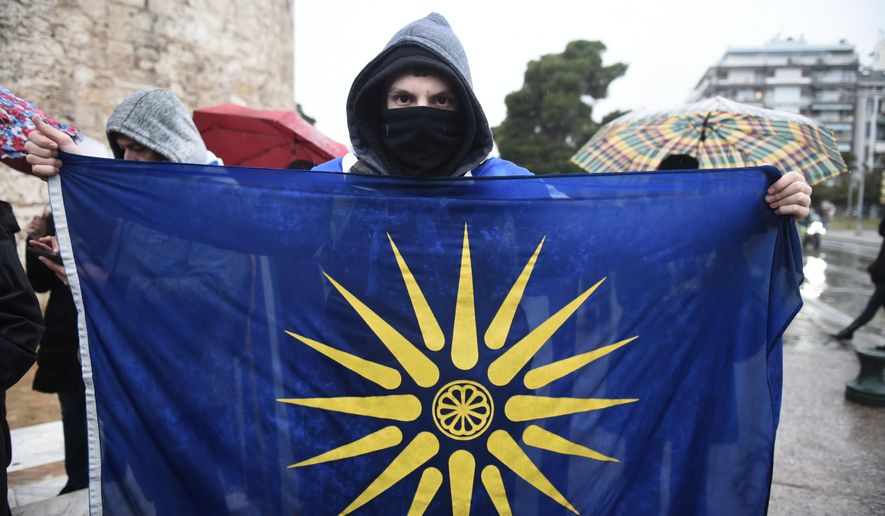 Holding a flag with the Star of Vergina, the emblem of the ancient Greek kingdom of Macedonia and Alexander the Great, an opponent of Prespa Agreement attends a rally in the northern port city of Thessaloniki, Greece, Friday, Jan. 25, 2019. Greek lawmakers have ratified the agreement for the country to drop its objections to neighbouring Macedonia joining NATO if the small country's name is changed to North Macedonia, ending a nearly three decade-long dispute that has kept Macedonia from joining the western military alliance and the European Union.(AP Photo/Giannis Papanikos)