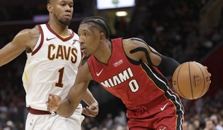 Miami Heat's Josh Richardson (0) drives past Cleveland Cavaliers' Rodney Hood (1) in the second half of an NBA basketball game, Friday, Jan. 25, 2019, in Cleveland. (AP Photo/Tony Dejak)