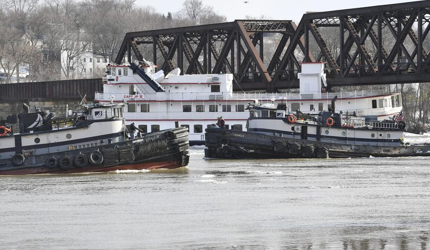 Crews from the tugboats Margot ,left, and Frances work to free the Captain JP III cruise ship that broke away from its winter moorings in Troy, N.Y., and floated down river and became wedged against the Livingston Avenue train bridge that spans the Hudson River in Albany, N.Y., Friday, Jan. 25, 2019. (AP Photo/Hans Pennink)