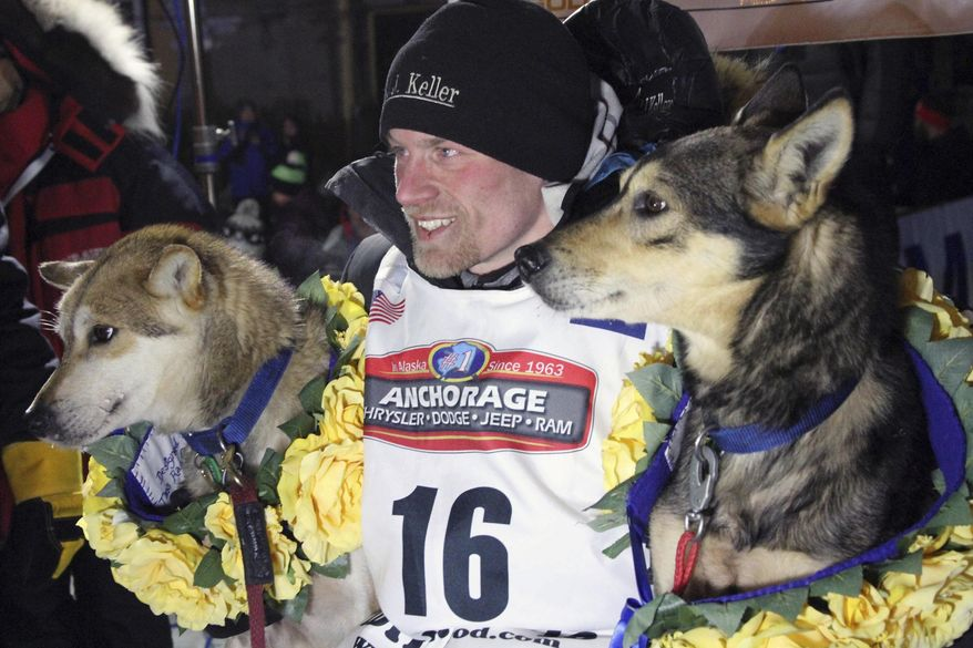 FILE - In this March 15, 2016, file photo, Dallas Seavey poses with his lead dogs Reef, left, and Tide after finishing the Iditarod Trail Sled Dog Race in Nome, Alaska. The four-time champion of the world's most famous sled dog race is skipping the Iditarod for the second straight year in favor of a race in Norway. Seavey on Friday, Jan. 25, 2019, said he plans to participate in the Finnmarkslopet this March. (AP Photo/Mark Thiessen, File)