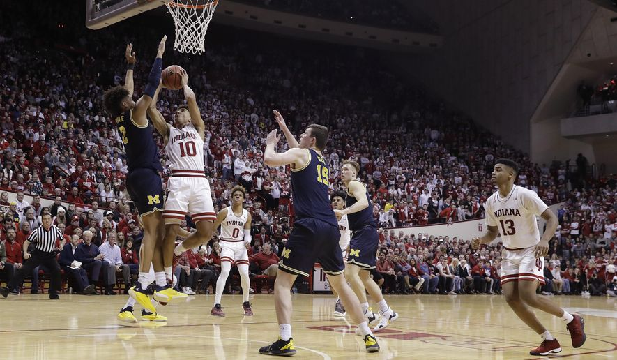 Indiana's Rob Phinisee (10) shoots against Michigan's Jordan Poole (2) during the second half of an NCAA college basketball game Friday, Jan. 25, 2019, Bloomington, Ind. Michigan won 69-46. (AP Photo/Darron Cummings)