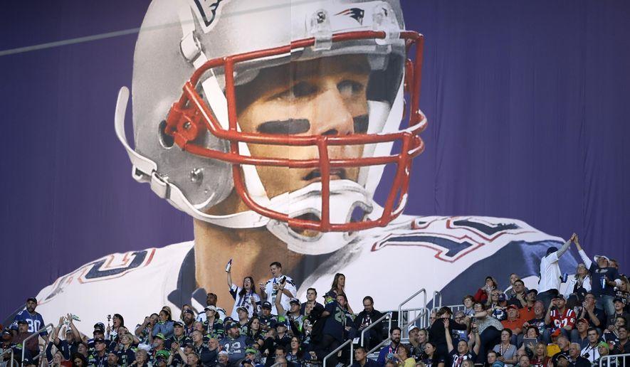 Fans cheer under a banner of New England Patriots quarterback Tom Brady (12) before the NFL Super Bowl XLIX football game between the Seattle Seahawks and the New England Patriots, in Glendale, Arizona, Feb. 1, 2015. (AP Photo/Matt Slocum) ** FILE **