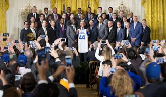 FILE - In this Feb. 4, 2016, file photo, President Barack Obama holds up Golden State Warrior basketball jersey given to him by team members during a ceremony in the East Room of the White House in Washington where he honored the 2015 NBA Champions. The Warriors had a meeting with former President Obama on Thursday, Jan. 24, 2019, at Obama's office in Washington before the defending NBA champs defeated the Washington Wizards. (AP Photo/Pablo Martinez Monsivais, File)