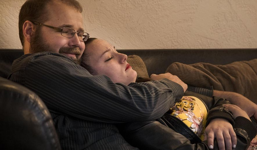 "In this Tuesday, Jan. 8, 2019 photo, Alternative touch therapist Eric Bale snuggles with trainee Roxanne Sears at Snuggle Buddiez in Boise, Idaho. A group of four ""snugglists"" with the new Boise-based company help clients who just need a hug or a cuddle companion without any emotional strings. (Darin Oswald/Idaho Statesman via AP)"