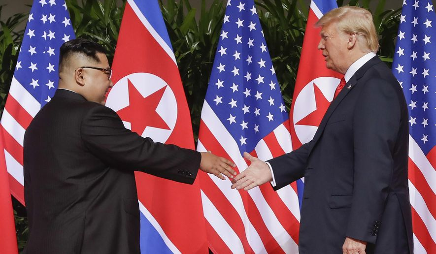 FILE - In this June 12, 2018, file photo, U.S. President Donald Trump reaches to shake hands with North Korea leader Kim Jong Un at the Capella resort on Sentosa Island in Singapore. (AP Photo/Evan Vucci, File)