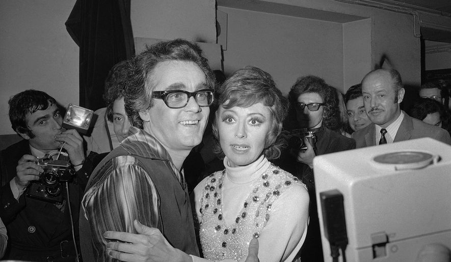 """FILE - In this Jan. 20, 1972 file picture French-born Italian singer, dancer and actress Caterina Valente, right, embraces Franco-Armenian musical composer, arranger, conductor and pianist Michel Legrand after their show at the Olympia in Paris, France. Oscar-winning composer and pianist Michel Legrand, whose hits included the score for """"The Umbrellas of Cherbourg"""" and the song """"The Windmills of Your Mind"""" and who left a lasting imprint on France's musical universe, has died at age 86. (AP Photo/Michel Lipchitz, File)"""