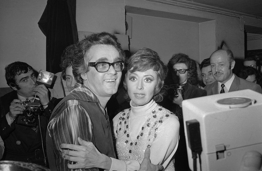 "FILE - In this Jan. 20, 1972 file picture French-born Italian singer, dancer and actress Caterina Valente, right, embraces Franco-Armenian musical composer, arranger, conductor and pianist Michel Legrand after their show at the Olympia in Paris, France. Oscar-winning composer and pianist Michel Legrand, whose hits included the score for ""The Umbrellas of Cherbourg"" and the song ""The Windmills of Your Mind"" and who left a lasting imprint on France's musical universe, has died at age 86. (AP Photo/Michel Lipchitz, File)"