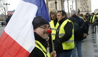 A Yellow vest demonstrator wearing a red nose gathers near the Arc de Triomphe before marching in Paris, Saturday, Jan. 26, 2019. France's yellow vest protesters are hitting the streets again, keeping up pressure on President Emmanuel Macron even as internal divisions and frustration over protest violence cloud the movement's future. (AP Photo/Michel Euler)