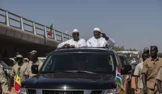 In this photo taken on Jan. 21, 2019, Senegal's President Macky Sall, center left, and Gambian President Adama Barrow, center right, drive past a newly inaugurated bridge in Banjul, Gambia. The leaders of Senegal and Gambia have cut the ribbon on a project that was decades in the making, a bridge that links the north and south banks of the Gambia River and ties the neighbors closer together. A boom in trade is expected for this part of West Africa. (AP Photo )