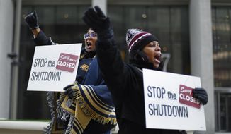 FILE - In this Jan. 10, 2019 file photo Cheryl Monroe, right, a Food and Drug Administration employee, and Bertrice Sanders, a Social Security Administration employee, rally to call for an end to the partial government shutdown in Detroit. The government shutdown left an especially painful toll for African-Americans who make up nearly 20 percent of the federal workforce and historically have been on the low end of the government pay scale. The U.S. Office of Personnel Management says African-Americans make up about 18 percent of the federal workforce of approximately 2.1 million employees. (AP Photo/Paul Sancya, file)