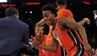 Illinois guard Ayo Dosunmu (11) celebrates with a coach after defeating No. 13 Maryland 78-67 in an NCAA college basketball game Saturday, Jan. 26, 2019, in New York. Illinois defeated Maryland 78-67. (AP Photo/Adam Hunger)
