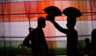 An Indian security personnel helps another with a headgear before participating in a parade to mark Republic Day in Gauhati, India, Saturday, Jan. 26, 2019. (AP Photo/Anupam Nath)