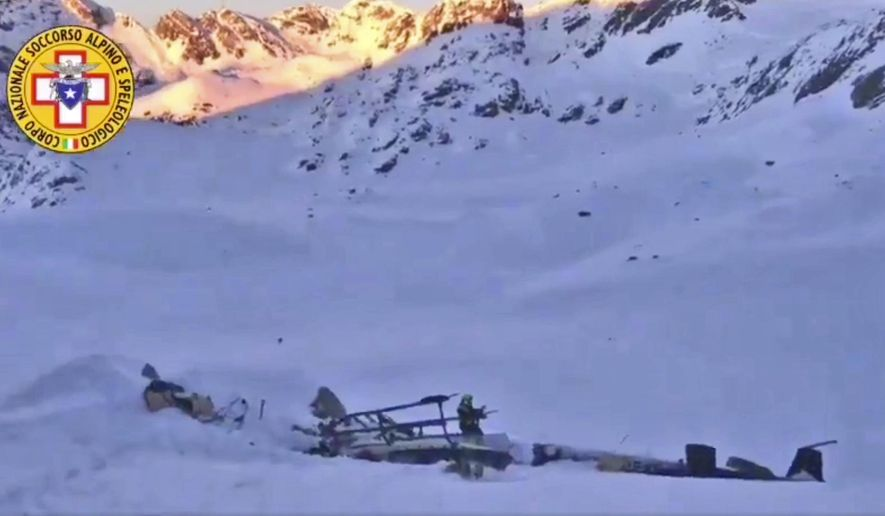 A rescuer stands next to the debris of an helicopter after a midair collision between a small tourist airplane and a helicopter carrying skiers to a glacier in the northwestern region of Val d'Aosta, Friday, Jan 25, 2019.  Italian alpine rescue officials say five people have been killed in the crash that took place over the Rutor Glacier. (Soccorso Alpino e Speleologico via AP)