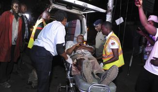 A man with minor injuries is taken away by paramedics from the scene of a small blast in Nairobi, Kenya, Saturday, Jan. 26, 2019.  An explosive device went off after a handcart pusher was given a small piece of luggage by an unknown person outside a cinema in a busy part of the capital Saturday night, injuring one person, a police officer said. (AP Photo/John Muchucha)