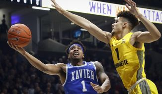 Xavier guard Paul Scruggs, left, shoots against Marquette forward Brendan Bailey in the first half of an NCAA college basketball game, Saturday, Jan. 26, 2019, in Cincinnati. (AP Photo/John Minchillo)