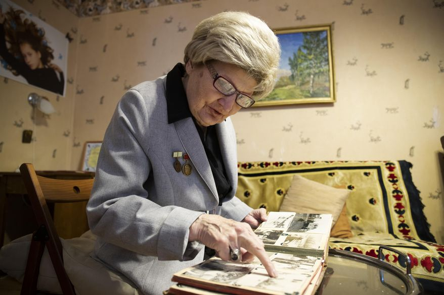 In this Wednesday, Jan. 23, 2019 photo, Tamara Chernykh, 81, a survivor of the Nazi siege of Leningrad during World War II, looks at her photo album in St. Petersburg, Russia. The Nazi siege of Leningrad lasted nearly 2 and a half years until the Soviet Army drove the Nazi troops away on Jan. 27, 1944. Estimates of the death toll vary, but historians agree that more than one million Leningrad residents died of hunger and air and artillery bombardment in one of the most horrifying episodes of World War II. (AP Photo/Dmitri Lovetsky)