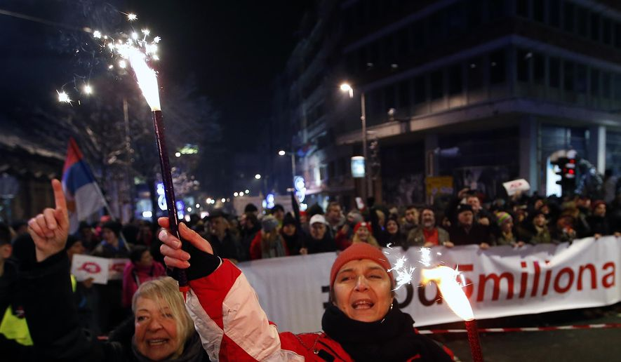 People light torches and march during a protest against populist President Aleksandar Vucic in Belgrade, Serbia, Saturday, Jan. 26, 2019. The protesters are seeking to keep up the pressure on Vucic whom they accuse of stifling hard-won democratic freedoms in the Balkan country that went through a series of wars in the 1990s'. (AP Photo/Darko Vojinovic)