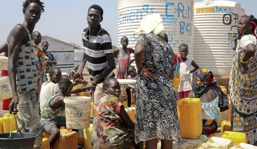 In this photo taken Tuesday, Jan. 22, 2019, residents of the Mangateen camp for the internally-displaced line up to get water from a borehole, on the outskirts of the capital Juba, South Sudan. Tens of thousands of people are still sheltering in United Nations protected camps across the country, the legacy of an unprecedented decision by a U.N. peacekeeping mission to throw open its doors to people fleeing war. (AP Photo/Sam Mednick)