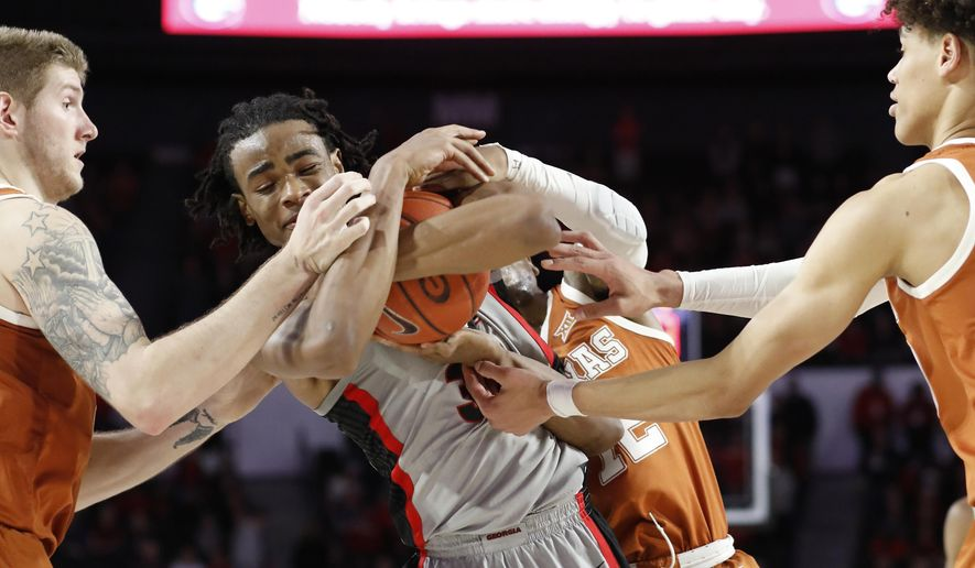 Georgia forward Nicolas Claxton (33) competes with Texas forward Dylan Osetkowski (21), guard Kerwin Roach II (12) and , forward Jaxson Hayes (10) to keep possession of the ball during an NCAA college basketball game in Athens, Ga., Saturday, Jan. 26, 2019. (Joshua L. Jones/Athens Banner-Herald via AP)