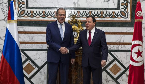Tunisian Foreign Minister Khemaies Jhinaoui, right, shakes hands with his Russian counterpart Sergey Lavrov during his visit, in Tunis, Tunisia, Saturday, Jan. 26, 2019. (AP Photo/Hassene Dridi)