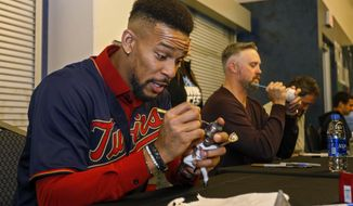 Minnesota Twins center fielder Byron Buxton autographs a bobblehead during the baseball team's TwinsFest on Friday, Jan. 25, 2019 in Minneapolis. (AP Photo/Bruce Kluckhohn)