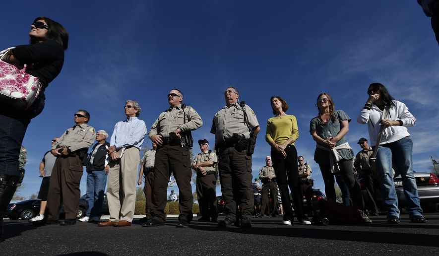 FILE - In this Jan. 9, 2013, file photo, parents from Anthem Elementary School stand with then Maricopa County Sheriffs Deputies and posse members, as they listen to Arpaio speak at Anthem Elementary School in Phoenix.  A committee of community leaders appointed by Arpaio's successor, Sheriff Paul Penzone, said Friday, Sept. 8, 2017,  that it has launched a review of the posse groups, which are lauded for saving taxpayers money but were criticized for serving as one of Arpaio's political tools.  (AP Photo/Ross D. Franklin, File)