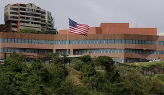 A U.S flag flies outside the U.S. embassy in Caracas, Venezuela, Thursday, Jan. 24, 2019. Venezuelans headed into uncharted political waters Thursday, with the young leader of a newly united and combative opposition claiming to hold the presidency and socialist President Nicolas Maduro digging in for a fight with the Trump administration. (AP Photo/Fernando Llano)