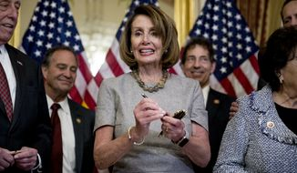 House Speaker Nancy Pelosi of Calif., accompanied by House Democratic members stand after signs a deal to reopen the government on Capitol Hill in Washington, Friday, Jan. 25, 2019. The measure now goes to the White House for President Donald Trump to sign.  (AP Photo/Andrew Harnik)