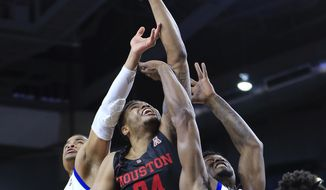 Houston's Breason Brady (24) battles Tulsa's Elijah Joiner and Martins Igbanu for a rebound during the first half of an NCAA college basketball game in Tulsa, Okla., Sunday, Jan. 27, 2019. (AP Photo/Dave Crenshaw)