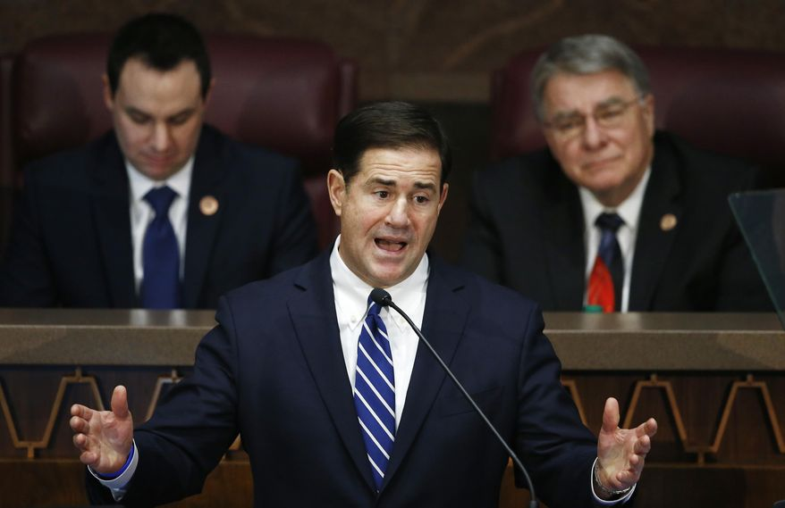 FILE - In this Jan. 8, 2018, file photo, Arizona Republican Gov. Doug Ducey, center, gives his state of the state address as he is flanked by House Speaker J.D. Mesnard, left, R-Chandler, and Senate President Steve Yarbrough, right, R-Chandler, at the capitol in Phoenix. Tax-filing season is just around the corner, but Arizona officials still don't know how they'll calculate your 2018 tax bill. That's because lawmakers punted last year on a routine vote to make the state and federal tax codes work together. (AP Photo/Ross D. Franklin, File)