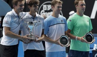 France's Nicolas Mahut , left, compatriot Pierre-Hugues Herbet pose with their trophy after defeating Finland's Henri Kontinen, right, and Australia's John Peers in the men's doubles final at the Australian Open tennis championships in Melbourne, Australia, Sunday, Jan. 27, 2019. (AP Photo/Aaron Favila)