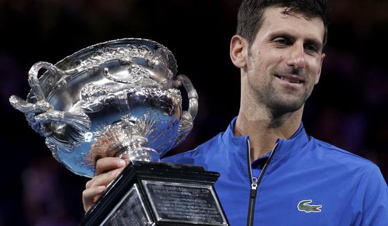 Serbia's Novak Djokovic holds his trophy after defeating Spain's Rafael Nadal in the men's singles final at the Australian Open tennis championships in Melbourne, Australia, Sunday, Jan. 27, 2019. (AP Photo/Aaron Favila)