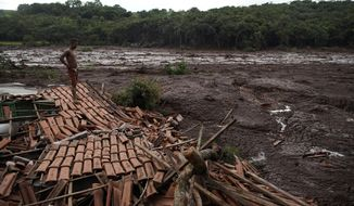 Emerson dos Santos stands on the debris of her mother's house in Brumadinho, Brazil, Saturday, Jan. 26, 2019. Rescuers in helicopters on Saturday searched for survivors while firefighters dug through mud in a huge area in southeastern Brazil buried by the collapse of a dam holding back mine waste, with at least nine people dead and up to 300 missing. Dos Santos' mother was not in the house and survived the tragedy. (AP Photo/Leo Correa)