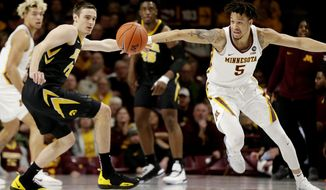 Iowa forward Nicholas Baer (51) and Minnesota guard Amir Coffey (5) vie for the ball during the first half of an NCAA college basketball game Sunday, Jan. 27, 2019, in Minneapolis. (AP Photo/Andy Clayton-King)