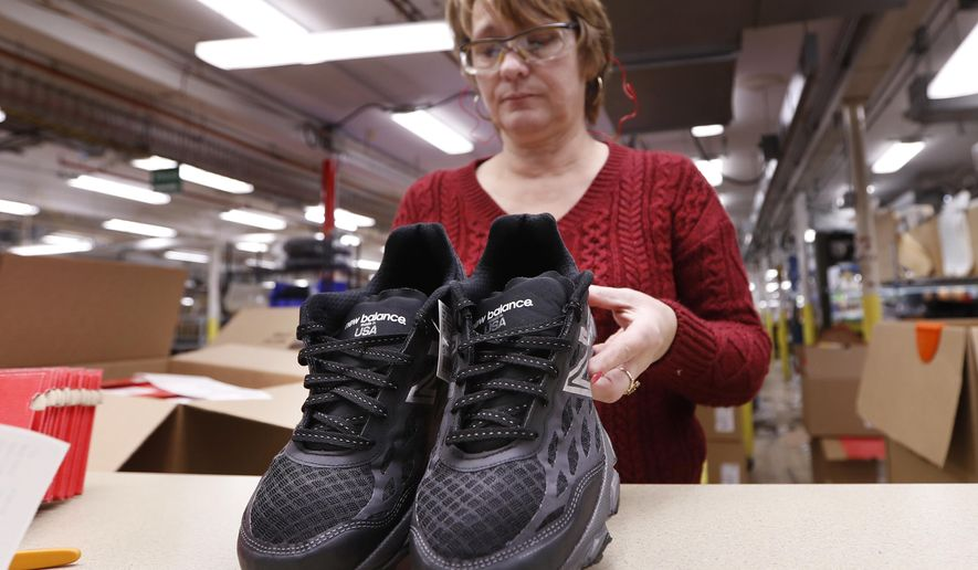 In this Monday, Dec. 17, 2018 photo, Ruby Williams inspects a pair of athletic shoes designed for the military at a New Balance factory in Norridgewock, Maine. The new contract fulfills a federal law requiring the military to outfit new recruits with American-made apparel. (AP Photo/Robert F. Bukaty)