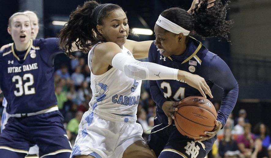 North Carolina's Stephanie Watts (5) reaches for the ball against Notre Dame's Arike Ogunbowale during the first half of an NCAA college basketball game in Chapel Hill, N.C., Sunday, Jan. 27, 2019. Notre Dame's Jessica Shepard (32) looks on. (AP Photo/Gerry Broome)