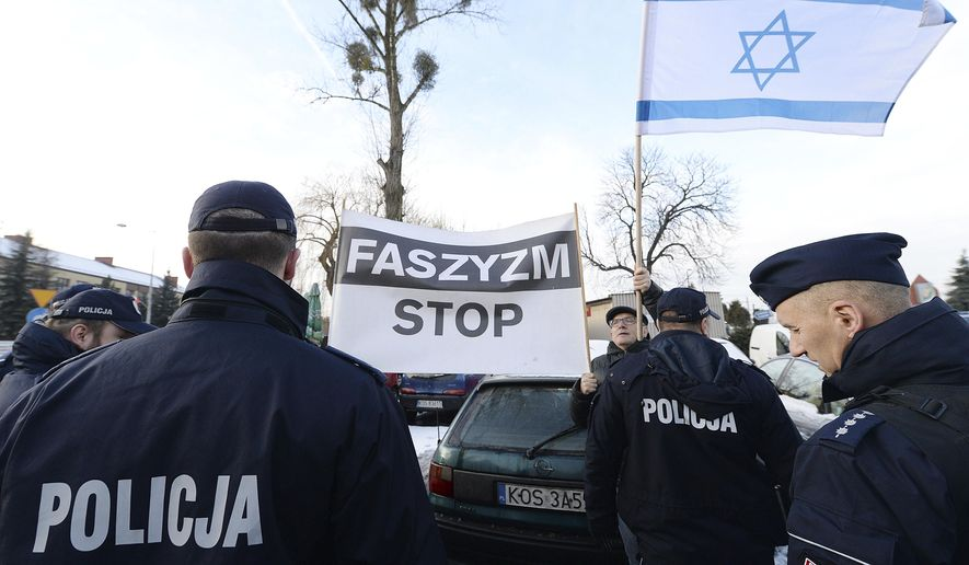 Police stand between anti-fascist protesters and a group of Polish nationalists who want to place a wreath at Auschwitz in honor of Poles murdered by the Germans, in Oswiecim, Poland, on Jan. 27, 2019. The nationalists are led by a far-right activist, Piotr Rybak, who has been imprisoned for burning the effigy of Jew. He calls it an act of protest against the Polish government, which he accuses of remembering only Jews and not murdered Poles in yearly observances at the memorial site. That claim is false. (AP Photo/Czarek Sokolowski)