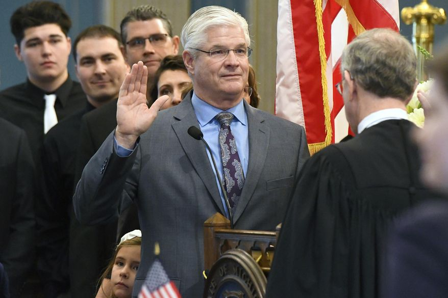 FILE - In this Jan. 9, 2019 file photo, Sen. Mike Shirkey, R-Clark Lake, is surrounded by his family on the floor of the Senate and sworn in by Chief Justice Stephen Markman during opening swearing in ceremonies for the State of Michigan 100th Legislature in Lansing, Mich.  Shirkey will lead Republicans in an era of divided government.  (Rod Sanford/Detroit News via AP)