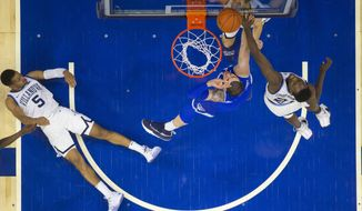 Seton Hall's Sandro Mamukelashvili, center, puts up the shot against Villanova's Dhamir Cosby-Roundtree, right, as Phil Booth, left, looks on from the court during the first half of an NCAA college basketball game, Sunday, Jan. 27, 2019, in Philadelphia. (AP Photo/Chris Szagola)