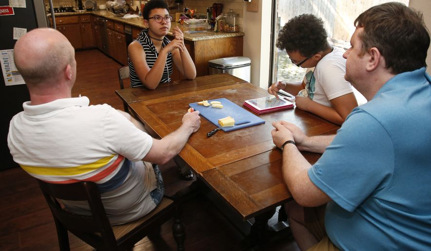 Sean Freiley (left) and husband Mitch Dailey listen to adopted daughter Jasmine Freiley in Bethany, Okla., Thursday, May 10, 2018, with her brother and adopted son Jerimiah McWilliams (second from right). The Oklahoma Legislature has passed a bill that LGBTQ advocates say would allow religious-based adoption agencies to discriminate against same-sex couples, single people and non-Christians. (AP Photo/Sue Ogrocki) ** FILE **