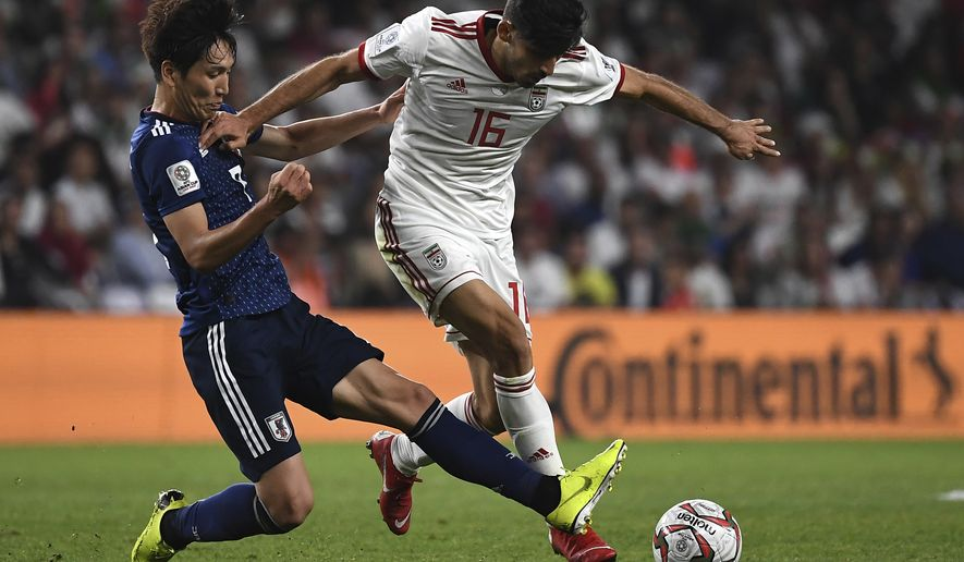 Iran's forward Sardar Azmoun, right, fights for the ball against Japan's midfielder Genki Haraguchi, left, during the AFC Asian Cup semifinal soccer match between Iran and Japan at Hazza Bin Zayed Stadium in Al Ain, United Arab Emirates, Monday, Jan. 28, 2015. Japan beat Iran 2-0. (AP Photo/Hassan Ammar)