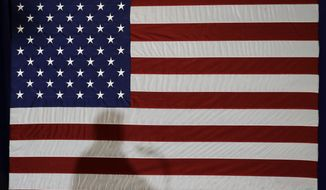In this Aug. 31, 2018, file photo, President Donald Trump's shadow is shown on an American flag as he speaks before signing an executive order at the CPCC Harris Conference Center in Charlotte, N.C. (AP Photo/Chuck Burton, File) **FILE**