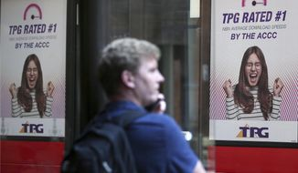 A bus branded with TPG ads goes past as a man uses his phone at a bus stop in Sydney, Tuesday, Jan. 29, 2019. TPG Telecom said it had abandoned the rollout of what would have been Australia's fourth mobile network because of the government's ban on Chinese giant Huawei, which would have been the main equipment vendor. (AP Photo/Rick Rycroft)