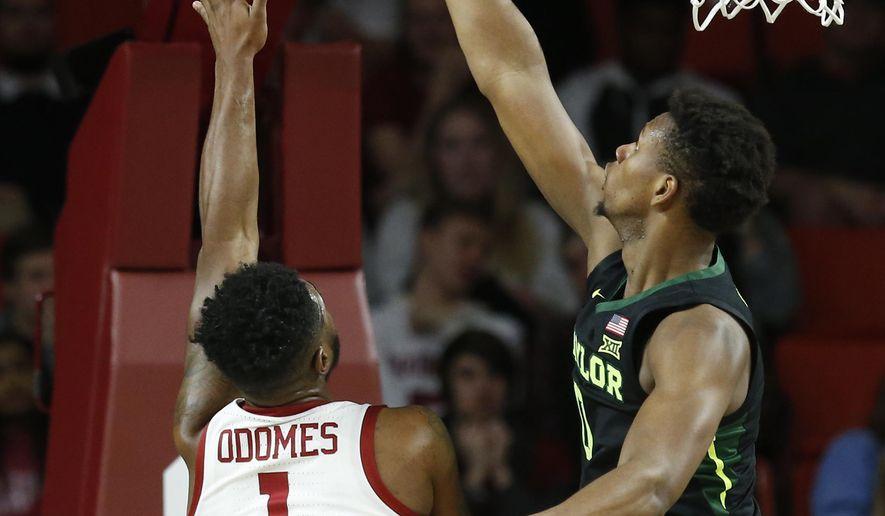 Baylor forward Flo Thamba, right, blocks a shot by Oklahoma guard Rashard Odomes (1) in the first half of an NCAA college basketball game in Norman, Okla., Monday, Jan. 28, 2019. (AP Photo/Sue Ogrocki)